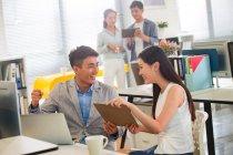 Sorridente giovane uomo d'affari asiatico e donna d'affari che lavorano insieme in ufficio — Foto stock