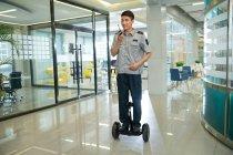 Улыбаясь молодых азиатских охранник верхом самобалансировки скутер и с помощью рации в офисе — стоковое фото