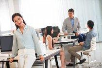 Hermosa feliz joven asiático mujer de negocios sonriendo en cámara mientras colegas trabajando detrás en oficina - foto de stock