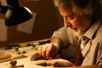Крупный план концентрированного зрелого ювелирного дизайнера, работающего с инструментами в мастерской — стоковое фото