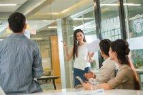 Giovani colleghi d'affari che guardano una donna d'affari sorridente che tiene documenti e parla durante la presentazione in ufficio — Foto stock