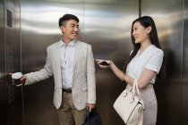 Young businessman with coffee to go and businessman with smartphone smiling each other in elevator — Stock Photo