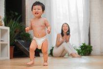 Счастливая молодая мать хлопая в ладоши и глядя на ее очаровательный ребенок малыш начинает ходить дома — стоковое фото