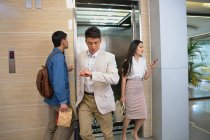 Busy young colleagues walking near elevator in office — Stock Photo