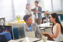 Jovens colegas sorridentes conversando e olhando uns para os outros enquanto trabalham juntos no escritório — Fotografia de Stock