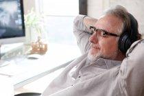 Architecte mature détendu dans les lunettes et écouteurs assis avec les mains derrière la tête sur le lieu de travail — Photo de stock