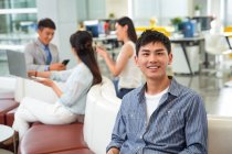 Handsome happy young businessman smiling at camera while colleagues working behind in office — Stock Photo