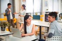 Sorridente giovane donna d'affari asiatica utilizzando il computer portatile e guardando il college maschile in ufficio moderno — Foto stock