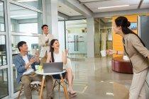 Felice giovane donna d'affari in possesso di una tazza di caffè e parlare con colleghi allegri utilizzando il computer portatile durante la pausa in ufficio — Foto stock