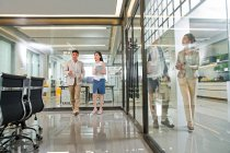 Professional young business colleagues walking and talking in modern office — Stock Photo