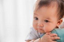 Recadrée shot de mère transportant adorable bébé asiatique à la maison — Photo de stock