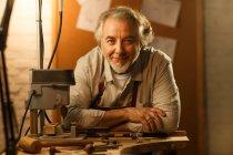 Профессиональный дизайнер ювелирных изделий в фартуке, склоняющийся за столом и улыбающийся на камеру в мастерской — стоковое фото