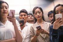 Grave jovem asiático pessoas usando smartphones no elevador — Fotografia de Stock
