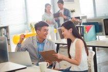 Sorridente giovani imprenditori asiatici utilizzando dispositivi digitali in ufficio — Foto stock