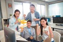 Felice giovane asiatico business team holding tazze e agitazione pugni in moderno ufficio — Foto stock