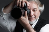 Professional male mature photographer working with photo camera — Stock Photo