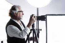 Vista lateral del fotógrafo masculino profesional trabajando con cámara de fotos en estudio - foto de stock