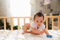 Adorabile asiatico bambino holding blu giocattolo e guardando fotocamera mentre giocare in culla — Foto stock