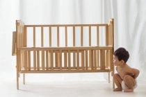 Полный вид восхитительного азиатского малыша в подгузнике, приседающего возле кроватки дома — стоковое фото