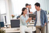Heureux jeune homme d'affaires et femme d'affaires en utilisant une tablette numérique et de discuter du travail au bureau — Photo de stock