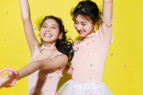 Schön glücklich stilvolle asiatische Freundinnen Spaß haben und tanzen auf gelbem Hintergrund mit bunten Konfetti — Stockfoto