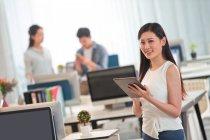 Bella giovane donna d'affari che tiene tablet digitale e sorride alla fotocamera in ufficio — Foto stock