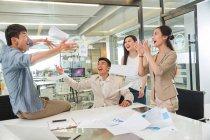 Animado jovem asiático negócios colegas jogando papéis no escritório moderno — Fotografia de Stock