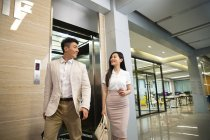 Happy young asian businessman and businesswoman smiling each other while walking from elevator in office — Stock Photo