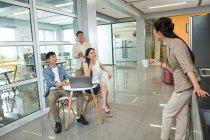 Jeune femme tenant la tasse de café et en regardant sourire collaborateurs utilisant l'ordinateur portable au bureau — Photo de stock