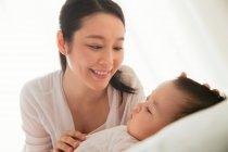 Счастливая молодая женщина смотрит на своего милого ребенка, спящего на кровати — стоковое фото