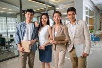 Холдинг блокноты и цифровых устройств, стоя вместе и улыбаясь в камеру в office профессиональный молодых бизнес-команда — стоковое фото