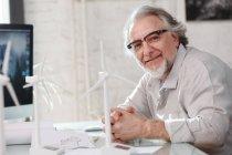 Architecte mature à lunettes, travailler avec des modèles de moulins à vent et souriant à la caméra dans le bureau — Photo de stock