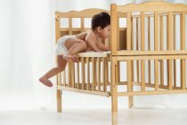 Вид в полный рост восхитительного малыша в пеленках, лазающего по кроватке — стоковое фото