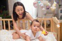Щаслива молода мати гумова качка і граючи з милою немовляти дитини лежачи в ліжечку — стокове фото