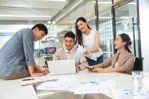 Улыбающиеся молодые азиатские бизнесмены, использующие ноутбук и работающие с бумагами в современном офисе — стоковое фото