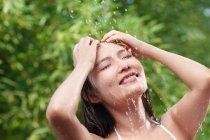 Красивая счастливая молодая азиатская женщина с закрытыми глазами принимает душ на зеленом природном фоне — стоковое фото