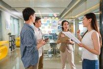 Jeunes entrepreneurs asiatiques professionnels discutant d'un nouveau projet au bureau — Photo de stock