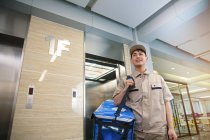 Low angle view of smiling young asian delivery man with bag walking from elevator in business center — Stock Photo