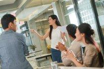 Giovane donna d'affari sorridente che tiene documenti e indica note sul vetro durante la presentazione, i colleghi applaudono in primo piano — Foto stock