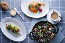 Top view of delicious dishes, drink and mussels in pan on table — Stock Photo