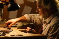 Вид сбоку профессионального ювелирного дизайнера в фартуке, сидящего на рабочем месте — стоковое фото