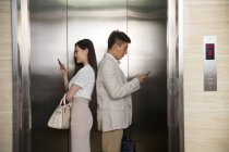 Side view of young asian businessman and businesswoman standing back to back and using smartphones in elevator — Stock Photo