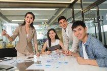 Felice giovane professionista asiatico business people working con papers e smiling a camera in ufficio — Foto stock