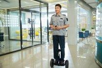 Улыбаясь молодой охранник верхом самобалансировки скутер и проведение рации в бизнес-центре — стоковое фото