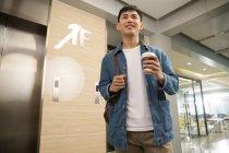 Низкий угол зрения улыбающийся молодой азиатский бизнесмен держит кофе, чтобы пойти в офис — стоковое фото