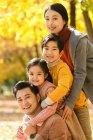 Glückliche Eltern mit zwei entzückenden Kindern, die gemeinsam in den Herbstpark lächeln — Stockfoto