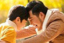 Vista laterale di felice padre asiatico e figlio toccare la fronte in autunno foresta — Foto stock