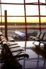 View of planes through window from empty airport lounge during sunset — Stock Photo
