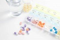 Высокий угол зрения таблетки в ежедневном контейнере на белой поверхности — стоковое фото