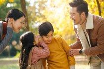 Sorridenti giovani genitori che guardano fratelli sussurrare qualcosa nel parco autunnale — Foto stock